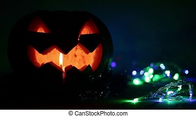 Closeup of scary holiday halloween carved glowing pumpkins. Flashing colored lights. Jack-O-Lantern