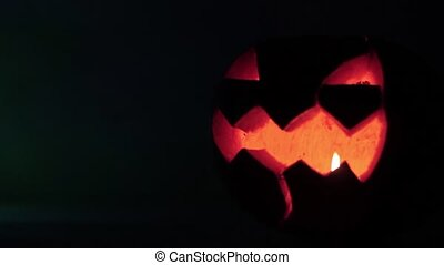 Closeup of scary holiday halloween carved glowing pumpkins. Jack-O-Lantern on dark background.
