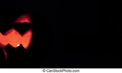 Closeup of scary holiday halloween carved glowing pumpkins. Jack-O-Lantern on dark background. Camera pan