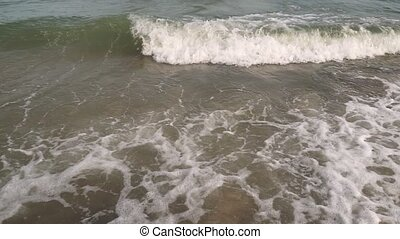 Closeup Of Sea Waves Washing Ashore A Sandy Beach. Slow motion.