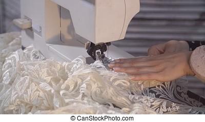 Closeup of seamstress machine-sewing a white textile