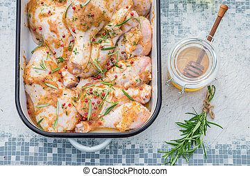Closeup of seasoning chicken legs with honey and herbs