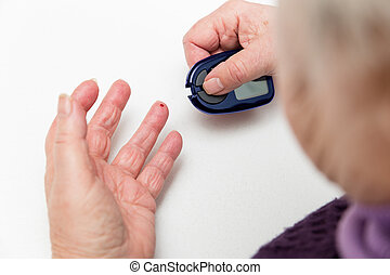 closeup of senior hands with glucometer