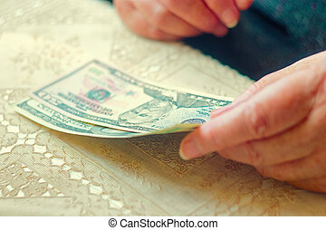 Closeup of senior lady with dollar bills in hands, toned image instagram-like color, selective focus, very shallow DOF