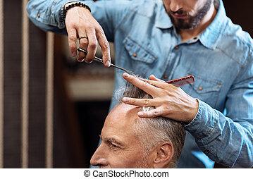 Closeup of senior man having haircut in barbershop