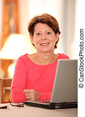 Closeup of senior woman at home with laptop computer