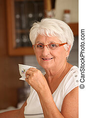 Closeup of senior woman with coffee cup