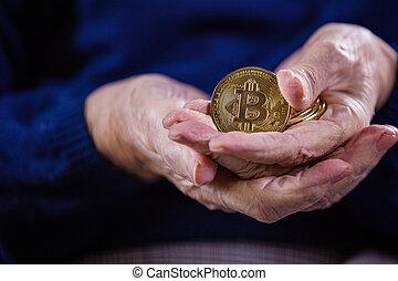 Closeup of senior woman's hands with bitcoins