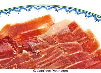 Closeup of serrano ham slices on a white dish. Jabugo. Spanish tapa.