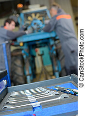 Closeup of set of spanners, mechanics in background