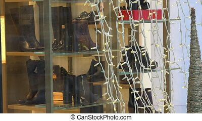 Closeup of shoes shop glass case with white string lights....