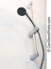 Closeup of shower head in bathroom.