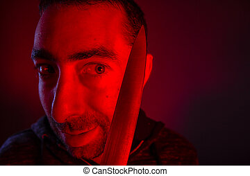 Closeup of sinister man looking at a knife that he holding