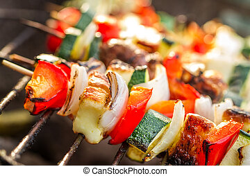 Closeup of skewers with chiken and vegetables on the grill