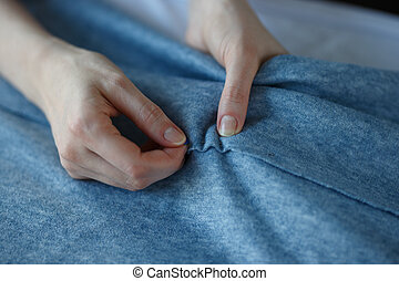 Closeup of skilled tailor hands marking and measuring fabric while making clothes.