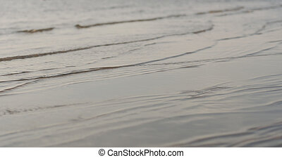 closeup of small waves on a beach at sunset