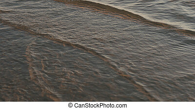 closeup of small waves with caustics on a beach at sunset
