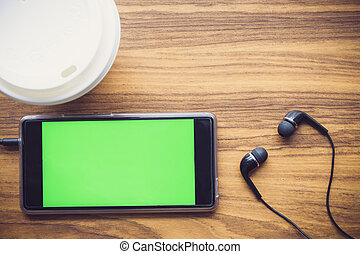 Closeup of smart phone with green screen and coffee cup.