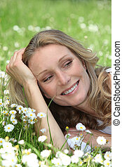 Closeup of smiling woman amongst the daisies