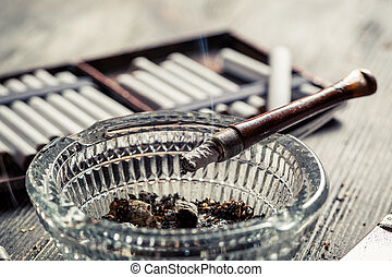 Closeup of smoke rising from a pipe in the ashtray