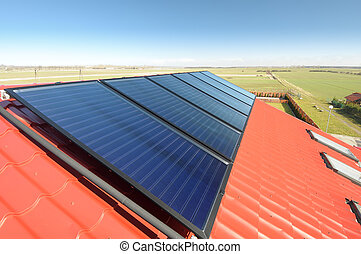 Closeup of solar panels on red tiled roof and beautiful blue sky.