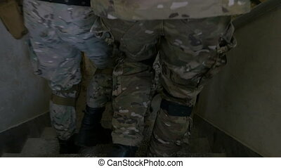 Closeup of soldier feet walking through abandoned building stairs in team exercise