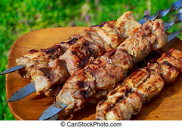 closeup of some meat skewers being grilled barbecue