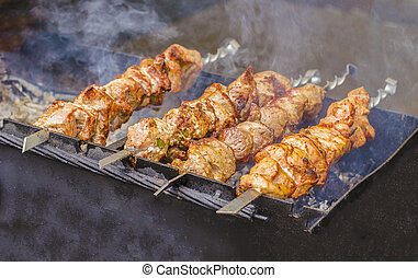 closeup of some meat skewers being grilled in a barbecue.