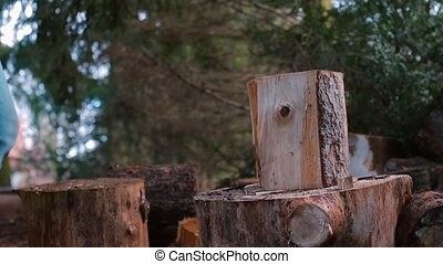 Closeup of splitting a wooden log with an ax.