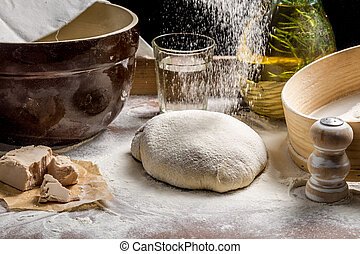 Closeup of sprinkling flour pizza dough