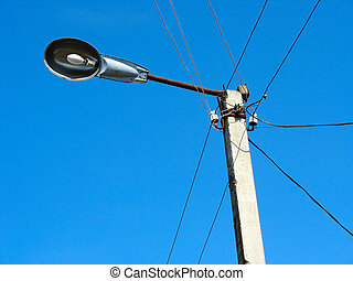 Closeup of street light lamp against a blue sky