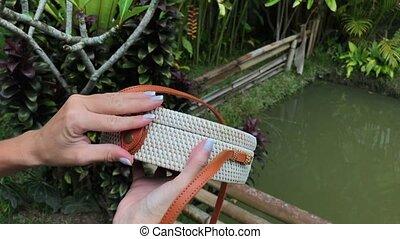 Closeup of stylish handmade rattan handbag on a tropical...