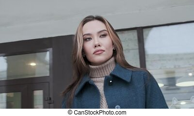 closeup of stylish asian girl in blue coat and turtleneck with long hair looking into distance thoughtfully and at camera outdoors. candid portrait of young attractive female. thoughtful woman posing