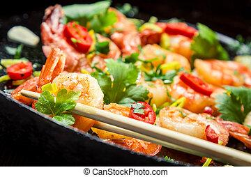 Closeup of tasting Fried shrimp with chopsticks