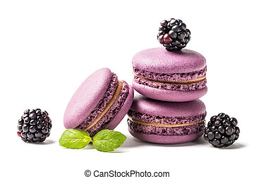 Closeup of tasty macaroons with blackberries on white background