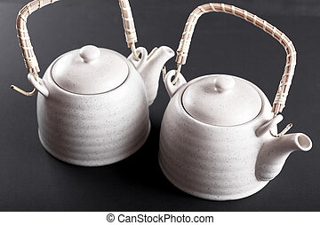 Closeup of tea set on black background.