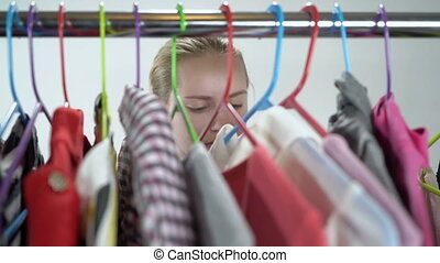 Closeup of teenage girl choosing her clothes on clothing rack in walk-in closet