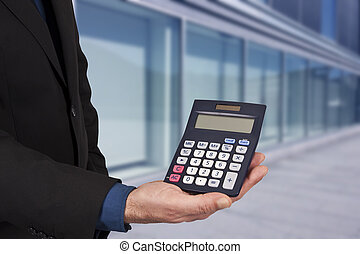 closeup of the calculator in hand, concept of finance and economics