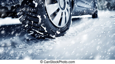Closeup of the car tire on winter road covered with snow in snowfall