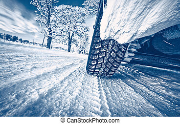 Closeup of the car tire on winter road covered with snow