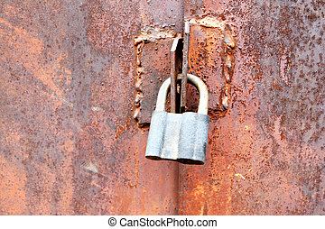 Closeup of the door lock on rusty metal stained gates