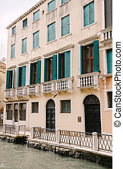 Closeup of the facade of a building, on the streets of Venice, Italy. The four-story building is sand-colored with green forged wooden shutters and balconies with white columns
