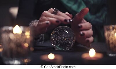 Closeup of the hand of a female magician conjuring over a glass ball among blurry burning candles in the dark. Concept of magic and evocation of spirits. Occultism and Sin
