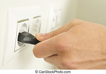 man plugging in or unplugging an electrical plug in a socket