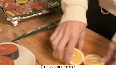 Closeup of the hands of the girl in the home kitchen lay out sliced lemon carols on a dish on a tray. Healthy home cooking