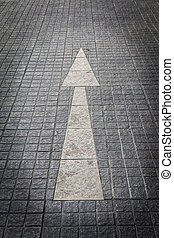 Closeup of the old white arrow on the tile floor 2
