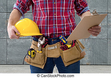 closeup of the worker of the construction with the helmet and the folder of the documents