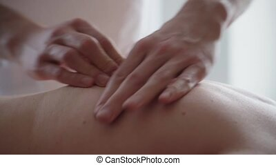 Closeup of Therapist doing back massage an attractive man...