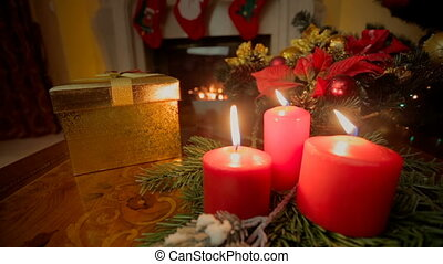 Closeup of three burning candles and golden Christmas gift...