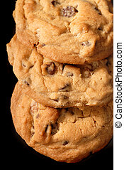 Closeup of three chocolate chip cookies on a dark reflective surface in verticle